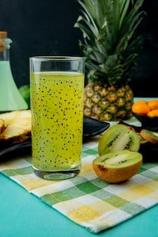 Suco de kiwi e kiwi com outras frutas na superfície do pano e na superfície preta