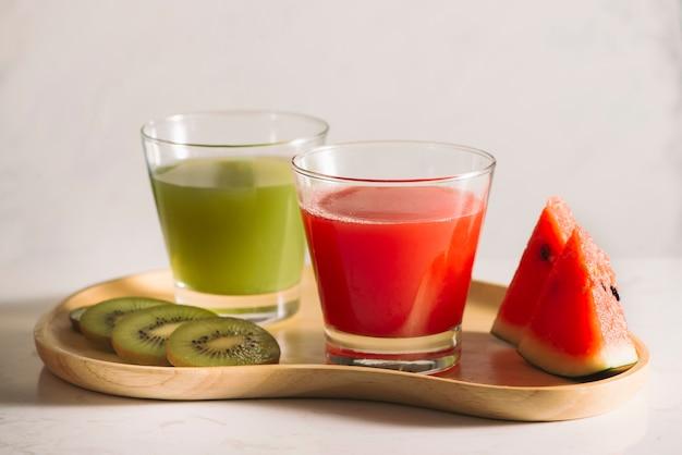 Suco de kiwi e melancia com fatias de frutas na bandeja de madeira