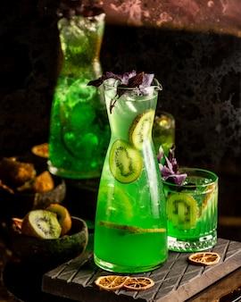 Suco de kiwi em uma jarra com folhas de manjericão