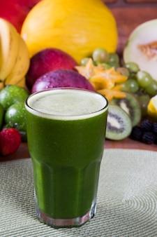 Suco de kiwi fresco com frutas no fundo.