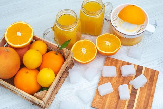 Suco de laranja com alguns cubos de gelo frescos e vista superior do espremedor de laranja