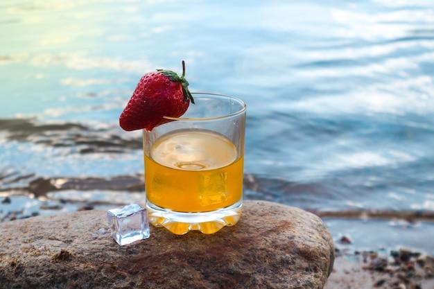 Suco de laranja com cubos de gelo e morangos em um copo na praia