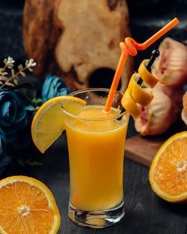 Suco de laranja com fatia e tubo vermelho em um copo.