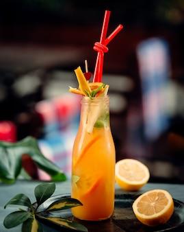 Suco de laranja com fatias de laranja e tubos vermelhos na garrafa