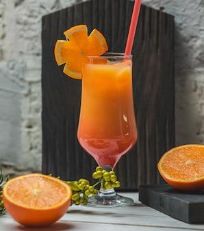 Suco de laranja com fatias em um copo com tubo vermelho.