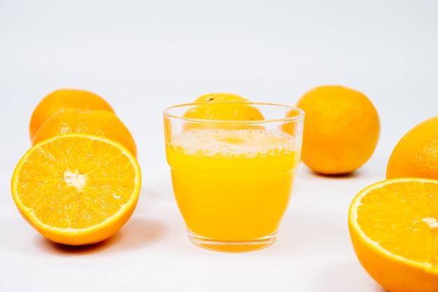 Suco de laranja com frutas, isolado na parede branca