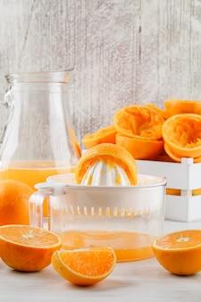 Suco de laranja com laranjas, espremedor de frutas em uma jarra na superfície branca