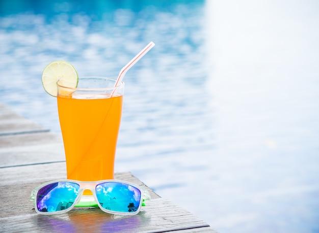 Suco de laranja com óculos de sol ao lado da piscina. férias, conceito de verão