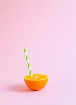 Suco de laranja com túbulo. laranja cortada ao meio no fundo rosa pastel.