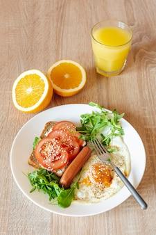 Suco de laranja com um prato de ovos fritos e sanduíche de legumes