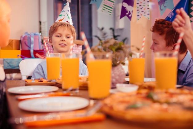 Suco de laranja. criança loira simpática expressando positividade enquanto espera pelos convidados