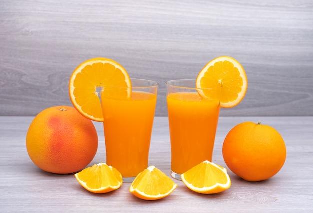 Suco de laranja decorado por todo e cortando laranja fresca na superfície de madeira