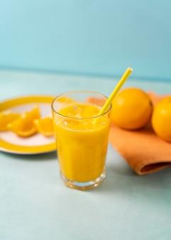 Suco de laranja delicioso com canudo em alto ângulo