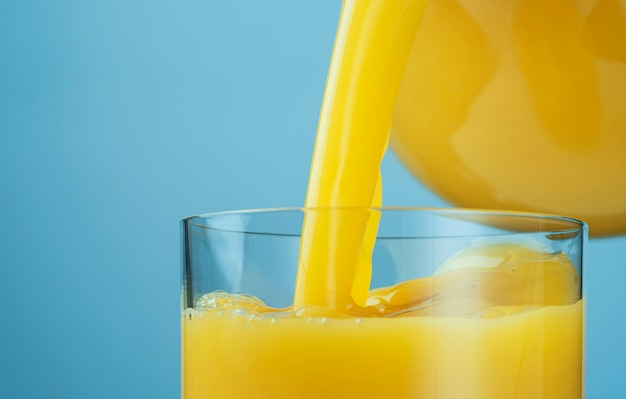 Suco de laranja despejando da jarra em um copo isolado em um fundo azul