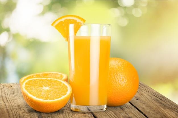 Suco de laranja e fatias de laranja no fundo