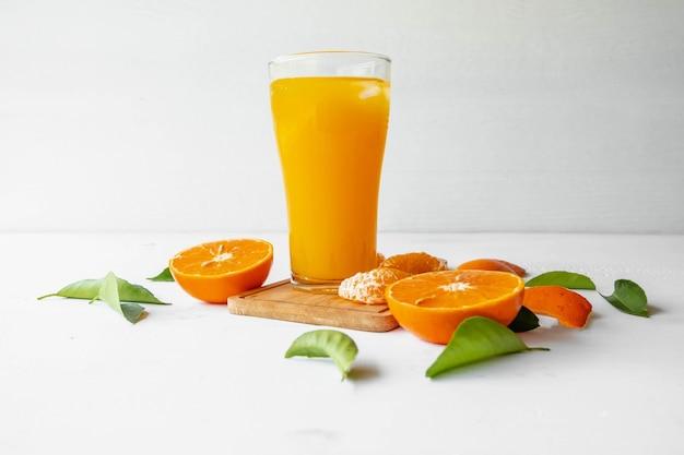 Suco de laranja e frutas frescas de laranja em uma mesa de madeira branca