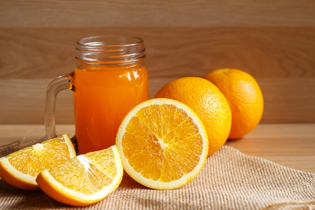 Suco de laranja e laranja em fundo de madeira