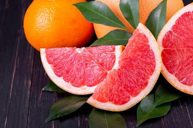 Suco de laranja e toranja em um fundo preto de madeira