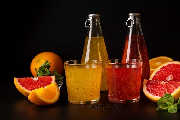 Suco de laranja e toranja tropical na moda com sementes de manjericão em garrafa na superfície preta