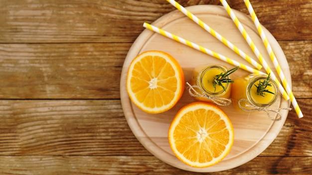 Suco de laranja em garrafas de vidro decoradas com um raminho de alecrim