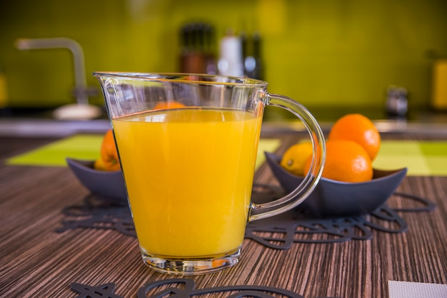 Suco de laranja em jarro e laranjas. alimentação saudável, alimentação, dieta e conceito vegetariano. suco de laranja na mesa de madeira