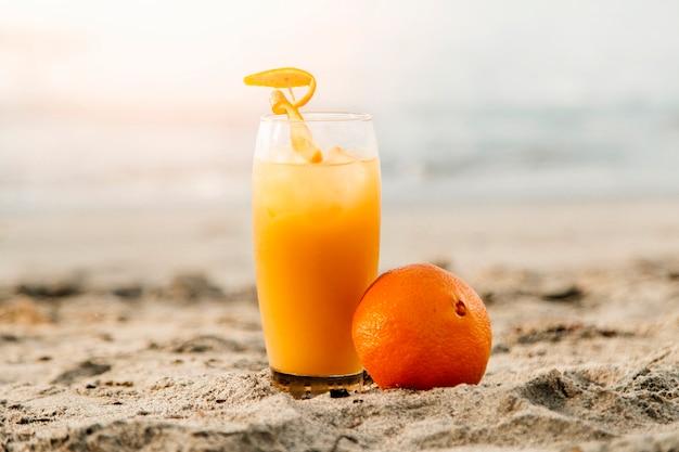 Suco de laranja em pé na areia