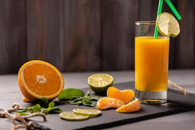 Suco de laranja em um copo com tubo em uma placa preta em um fundo escuro de madeira perto de hortelã-laranja