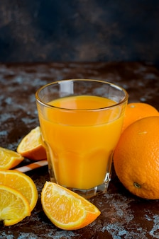 Suco de laranja em um copo e pedaços