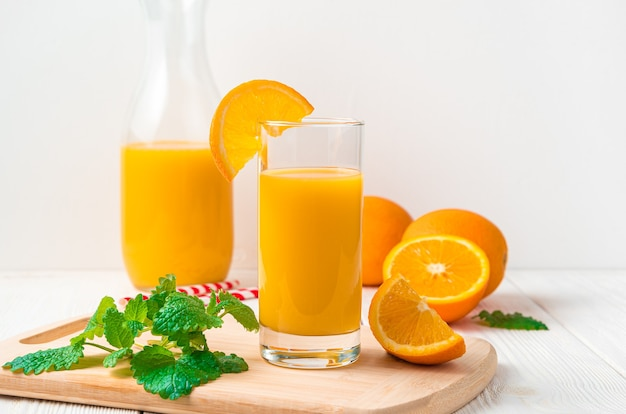 Suco de laranja em um copo na mesa de laranjas frescas. vista lateral