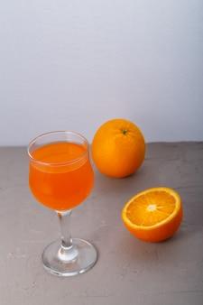 Suco de laranja em um copo perto de laranjas em uma superfície cinza foto vertical