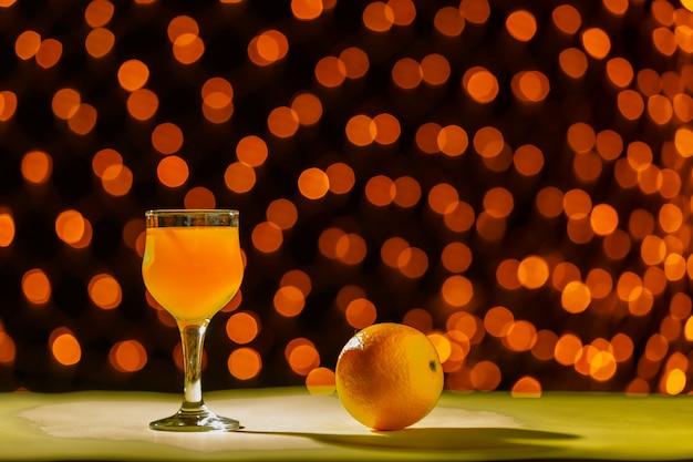 Suco de laranja em um copo perto de laranjas em uma superfície preta de luzes borradas