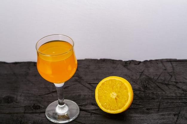 Suco de laranja em um copo perto de laranjas em uma superfície preta