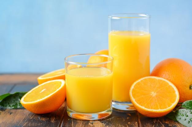 Suco de laranja em um óculos na mesa de madeira velha.