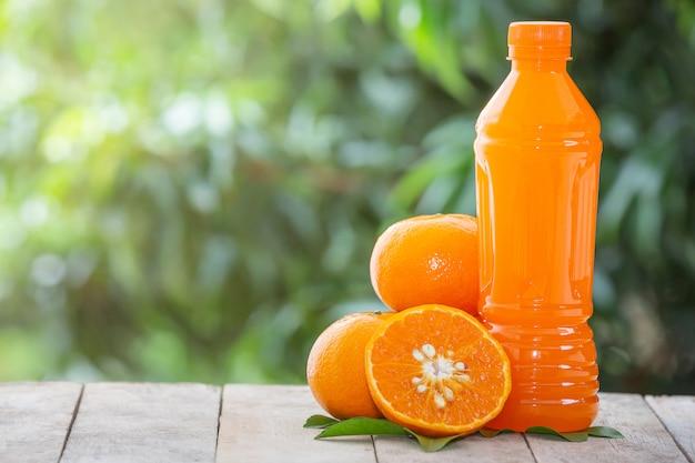 Suco de laranja em uma garrafa e laranjas