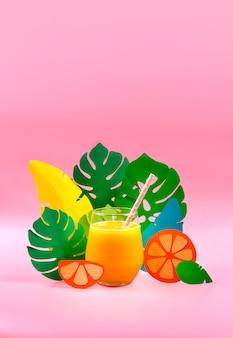 Suco de laranja em uma grama com folhas de papel e laranja no lado. conceito tropical foco seletivo.