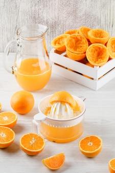 Suco de laranja em uma jarra com laranjas, espremedor vista de alto ângulo na superfície de madeira