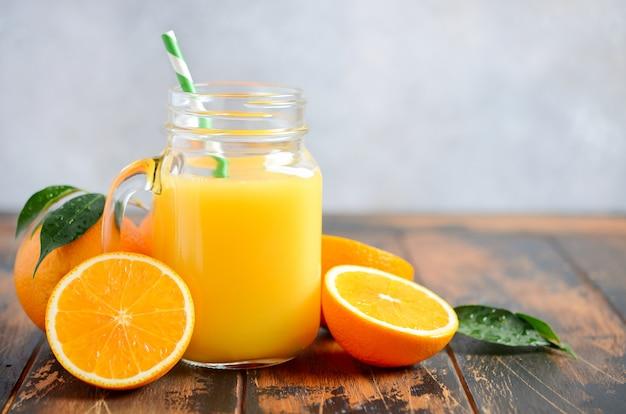 Suco de laranja em uma jarra em uma mesa de madeira.