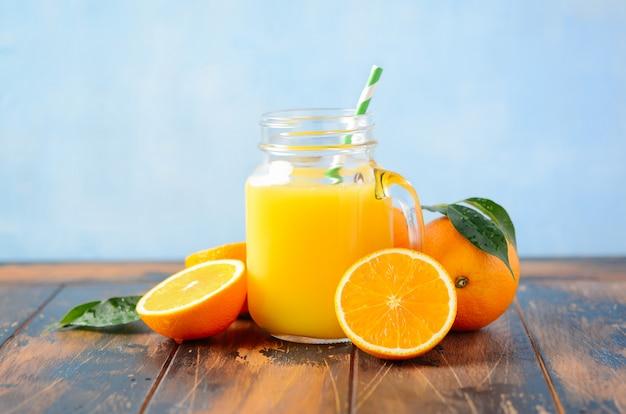 Suco de laranja em uma jarra na mesa de madeira velha.