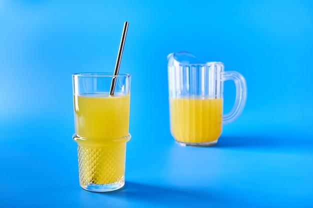 Suco de laranja em vidro com canudo e em jarra de vidro sobre fundo azul refrescante cópia de bebida de verão
