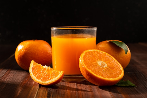 Suco de laranja em vidro e laranjas