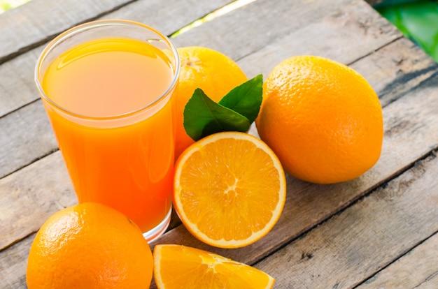 Suco de laranja em vidro, frutas frescas em fundo de madeira