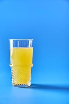Suco de laranja em vidro sobre fundo azul bebida refrescante de verão cópia espaço para seu texto vertical