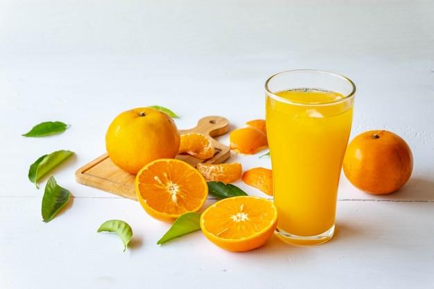 Suco de laranja espremido na hora e frutas de laranja cortadas ao meio Foto Premium