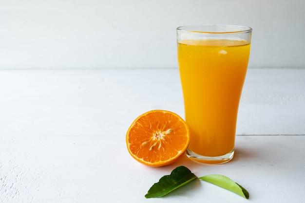 Suco de laranja espremido na hora e frutas de laranja cortadas ao meio