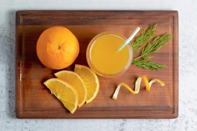 Suco de laranja fresco com frutas fatiadas ou inteiras na placa de madeira.