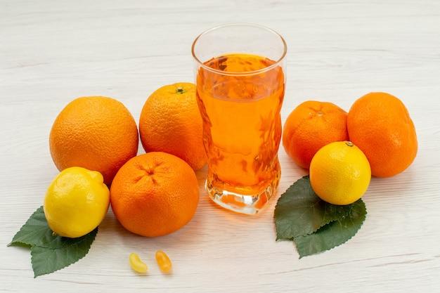 Suco de laranja fresco com laranjas e frutas cítricas na mesa branca