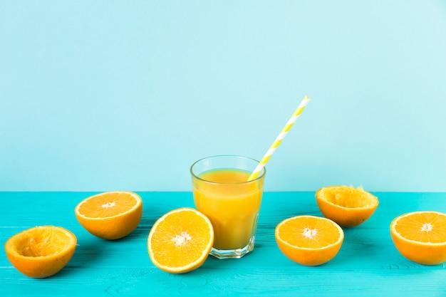 Suco de laranja fresco com palha na mesa azul