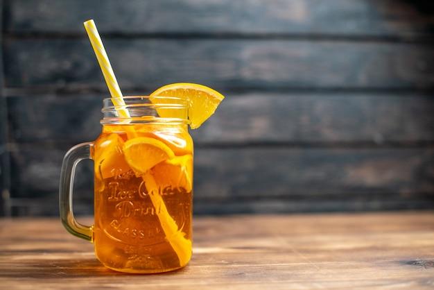 Suco de laranja fresco dentro da lata com canudo na foto colorida de fruta em barra escura