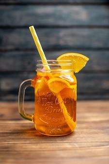 Suco de laranja fresco dentro de uma lata com canudo na mesa de madeira