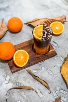Suco de laranja fresco e frutas cítricas a vitamina c tem benefícios para a saúde, fresco, em flocos, doce, organizado em uma bandeja de madeira, folhas e cubos de gelo redondos.